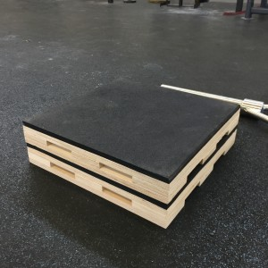 A Pair of stacked , heavy duty,rubber topped dead lifting blocks in front of a heavy barbel loaded with weights