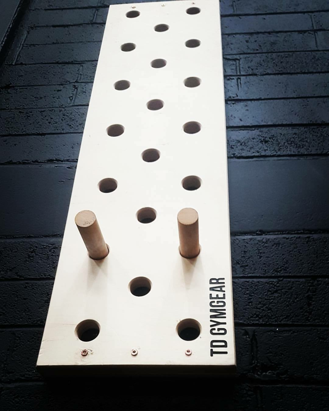 a board with multiple hole and two wooden pegs mounted on a dark wall