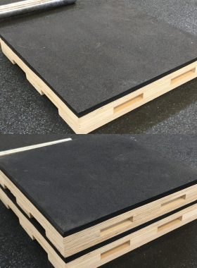 A Pair of stacked heavy duty rubber topped dead lifting blocks in front of a heavy barbel.