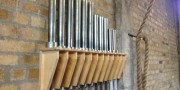 10 weight lifting barbells on a wooden barbell rack on yellow brick wall