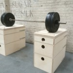a close front on view of a set of 3 tiered jerk block sections on the floor of a warehouse with a heavy barbell on top