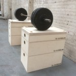 3 tiered jerk block sections on the floor of a warehouse with a heavy barbell on top